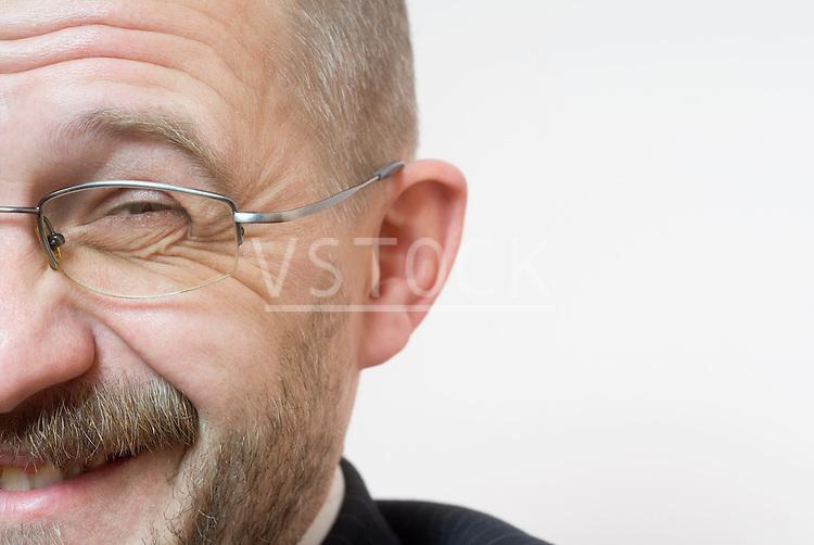 Man wearing glasses laughing, close-up