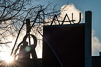 "UAA signage with the sun peeking behind the College of Engineering's new art installation ""Changing the World"" by Artist Patrick Garley."