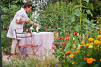 A guest laying the table on a small patio in the herb garden for an evening dinner