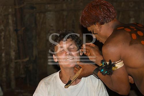 Xingu Indigenous Park, Mato Grosso State, Brazil. Aldeia Waura. Warrior applying face paint to Patrick Cunningham.