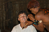 Xingu Indigenous Park, Mato Grosso State, Brazil. Aldeia Waura. Warrior applying face paint to Patrick Cunningham.