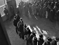 Shuffle With Tired Feet: Line of men inside a division office of the State Employment Service office at San Francisco, California, waiting to register for benefits on one of the first days the office was open. January 1938.<br /> <br /> Photo by Dorothea Lange.