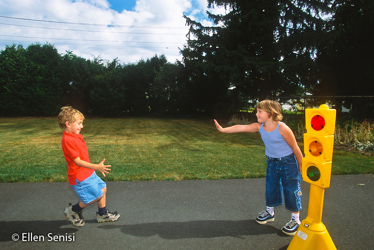"""MR / Schenectady, NY. Friends (boy left: age 6; boy right: age 5.) play stop and go game with toy traffic light. This picture illustrates """"stop."""" MR: Lan3, Col5. ID: AJ-LC. © Ellen B. Senisi"""