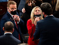 """United States Representative Marjorie Taylor Greene (Republican of Georgia) pulls down her mask, which reads """"Trump won,"""" to speak with a colleague as they await swearing in on the opening day of the 117th Congress at the U.S. Capitol in Washington, DC on January 03, 2021.<br /> CAP/MPI/RS<br /> ©RS/MPI/Capital Pictures"""
