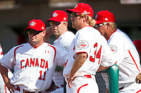 Team Canada coach Tim Leiper #34 huddles with his fellow coaches during an exhibition game against Team Canada at the USA Baseball National Training Center on September 29, 2011 in Cary, North Carolina.  (Brian Westerholt / Four Seam Images)