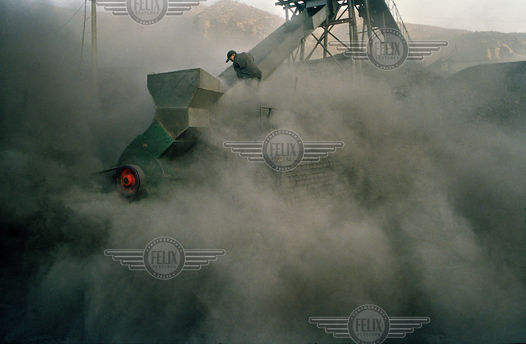 A worker stands by the conveyor belt in a small coal mine.  Shanxi is the largest producer of coal in China.  The rate of coal mining in the country is increasing from an annual production of over 2 billion tons in order to cater for China's rapid economic growth.