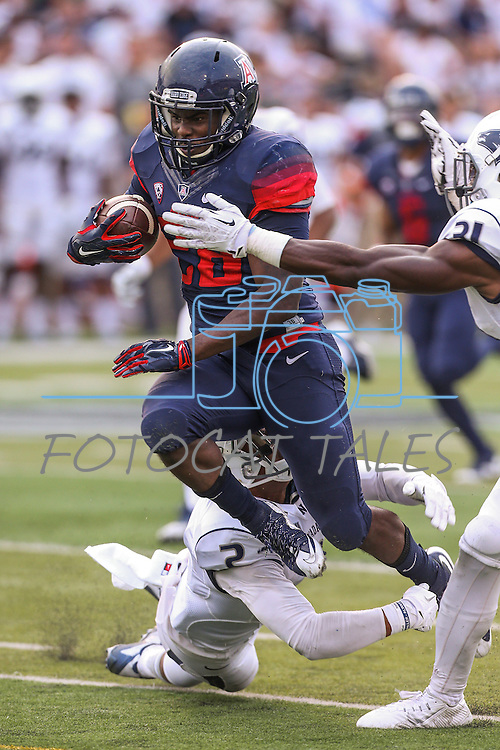 Arizona running back Nick Wilson (28) runs against Nevada defenders Asauni Rufus (2) and Randy Uzoma (31) during the first half of an NCAA college football game in Reno, Nev. on Saturday, Sept. 12, 2015. (AP Photo/Cathleen Allison)