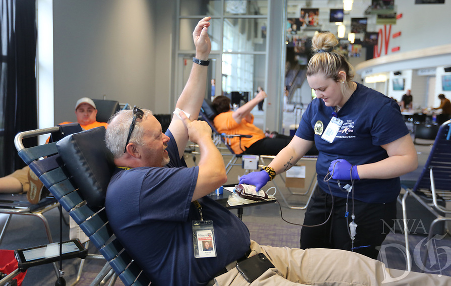 Chloe Alaire, donor specialist with Community Blood Center of the Ozarks, monitors fire marshal Jeremy Ashley, Tuesday, June 8, 2021, during the Boots and Badges Blood Donor Drive at Cross Church Fayetteville. The drive, hosted by the Community Blood Center of the Ozarks is a friendly competition between the Fire Department and the Police Department. Check out nwaonline.com/210609Daily/ and nwadg.com/photos for a photo gallery.<br /> (NWA Democrat-Gazette/David Gottschalk)