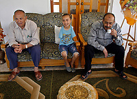 """Gaza.June.09.2008.Aya Masouad 8 years born without arms,use here toes and feet to go around with her daily life,shesit behind her father. she easts or drink with her toes , she love her life and thanking God, she practice her life as she is normel people . """" Photo by Fady Adwan/propaimages"""""""