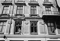 Denmark. Capital Region. Copenhagen. A woman is enjoying the sun and reading a book while seated on a cushion outside on her living room's window sill. 5.08.2016  © 2016 Didier Ruef