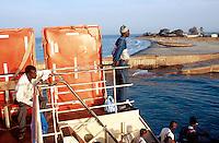 Gambia. Barra. Ferry on the Atlantic ocean. Men on a ferry ride at sunrise.  © 2000 Didier Ruef