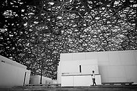 United Arab Emirates (UAE). Abu Dhabi. A filipino man works as a guardian at the Louvre Abu Dhabi which is an art and civilization museum. The museum is part of a thirty-year agreement between the city of Abu Dhabi and the French government. The museum is located on the Saadiyat Island Cultural District. It is approximately 24,000 square metres in size, with 8,000 square meters of galleries, making it the largest art museum in the Arabian peninsula. Jean Nouvel (born 12 August 1945), a French architect, has conceived the Louvre Abu Dhabi. Now considered as one of the modern urban wonders of the world, Louvre Abu Dhabi is not only the Arab world's first universal museum but a powerful symbol of the United Arab Emirates' ambition and achievement. The centre piece of Nouvel's vision is a huge silvery dome that appears to float above the museum-city. Despite its apparent weightlessness, the dome weighs around 7,500 tonnes. Inspired by the cupola, a distinctive feature in Arabic architecture, Nouvel's dome is a complex, geometric structure of 7,850 stars. These stars are repeated at various sizes and angles in eight different layers. As the sun passes above, its light filters through the perforations in the dome to create an enchanting effect within the museum, known as the 'rain of light'.  The United Arab Emirates (UAE) is a country in Western Asia at the northeast end of the Arabian Peninsula. 21.02.2020  © 2020 Didier Ruef