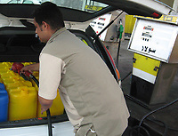 "A Palestinian man fills jerry-cans at a gas station in Gaza City, Sunday, June 17, 2007. Israeli fuel company Dor Alon said Sunday it was cutting off supplies to Gaza gas stations following the takeover of the territory by Hamas militants. But it said it would continue to ship fuel to Gaza's electricity power plant.""photo by Fady Adwan"""