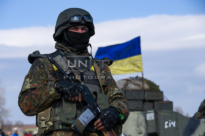 Ukrainian soldier stands on guard, while preparing for departure of the convoy during the withdrawal of heavy weapons. Near Artemovsk, Eastern Ukraine. Friday, 27 February 2015.
