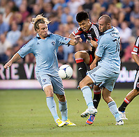 Long Tan (27) of D.C. United fights for the ball with Michael Harrington (2)  and Aurelien Collin (78) of Sporting Kansas City during the game at Livestrong Sporting Park in Kansas City, Kansas.  D.C. United lost to Sporting Kansas City, 1-0.