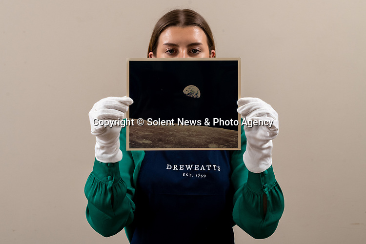 Pictured: Sales Coordinator Lulu Randall holds up 'Apollo 8. Earthrise', an original print of the first colour photograph of the Earth rising above the Moon's horizon taken in 1968 with an estimated value of £3,000-£5,000 ahead of auction today [WEDNESDAY]  at Dreweatts Auction House in Newbury, Berks.<br /> <br /> Taken by William Anders on December 24, 1968, it is the most famous view of planet earth and is the first photograph of 'earthrise' taken by human hand. It was the view observed by the Apollo 8 crew during the fourth orbit of the moon.<br /> <br /> Some of the most historic photographs chronicling the history of man's exploration of space, from early expeditions, to some of the latter trips of the 1990s will be sold at auction.  Over 600 images, many of which capture historic moments, such as the first humans in space, the first spacewalk and the first moon landing will be auctioned today on March 17th 2021 as part of the Space Exploration Photography and Ephemera auction by Dreweatts.<br /> <br /> © Jordan Pettitt/Solent News & Photo Agency<br /> UK +44 (0) 2380 458800