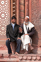 Fatehpur Sikri, Uttar Pradesh, India.  Two Men Talking outside Entrance to Jama Masjid (Dargah Mosque).  Wisdom being passed to the next generation.