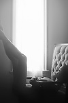 Fine art nude sensual black and white portrait of a beautiful woman with a dreamy expression lying naked by the window in an armchair with her legs raised up in glowing sunlight Image © MaximImages, License at https://www.maximimages.com