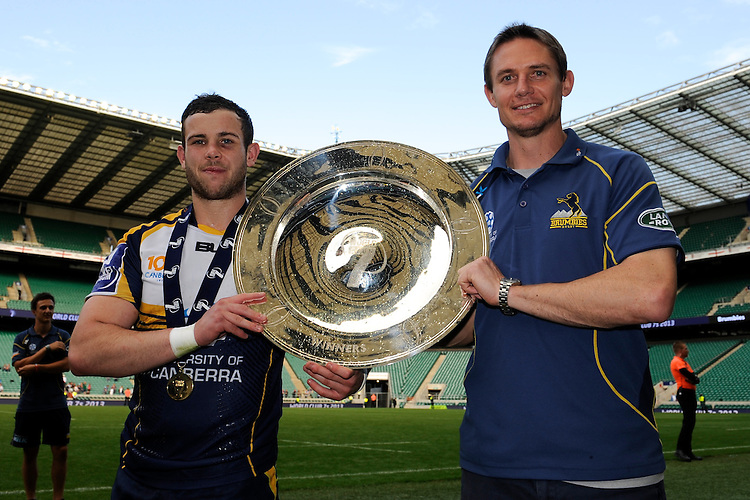 Robbie Coleman of the Brumbies (left) and Stephen Larkham lift the trophy after winning the World Club 7s Cup at Twickenham on Sunday 18th August 2013 (Photo by Rob Munro)