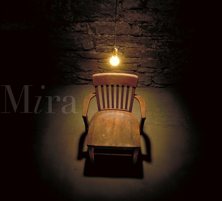 Interrogation room with wooden chair and bare lightbulb hanging directly overhead. United States.