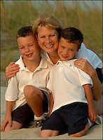 A family (model released) poses for a family portrait at sunset on a beach.