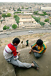 On the outer walls of Erbil Citadel overlooking surrounding Erbil, Kurdish boys play dama in June 2003.  Erbil, the capital of Iraqi Kurdistan, is one of the oldest continually inhabited city in the world.  (photo by Khampha Bouaphanh)