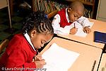 Parochial School Bronx New York  Kindergarten boy and girl sitting at desks writing in notebooks with pencil horizontal