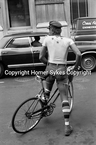 Gay African American man 1970s US. Dressed fashionably, tight short shorts long socks and peaked cap riding a bicycle Manhattan New York USA 1972