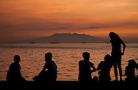 110516-N-DR144-408 MANILA, REPUBLIC OF THE PHILIPPINES (May 16, 2011) Manila residents watch sunset from sea wall while Nimitz-class aircraft carrier USS Carl Vinson (CVN 70) and Ticonderoga-class guided-missile cruisers USS Bunker Hill (CG 52) and USS Shiloh (CG 67) are at anchor in Manila Bay during a port visit to Manila, Republic of the Philippines.  Carl Vinson and Carrier Air Wing (CVW) 17 are underway in the U.S. 7th Fleet area of responsibility. (U.S. Navy photo by Mass Communication Specialist 2nd Class James R. Evans / Released)