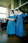 Nuns at St Mary at the Cross convent. Sister Mary Eanfleda Barbara OSB and Sister Mary Therese in their work overalls working in the ward of the old convent attached to Edgware Abbey Middlesex UK 1989 1980s<br />