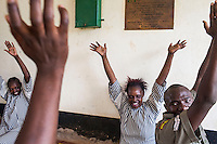 Prison guards, HIV positive women prisoners and  teachers from Africa Yoga Project practice yoga at a bi-weekly outreach at Langata Women's Prison in Nairobi, Kenya.
