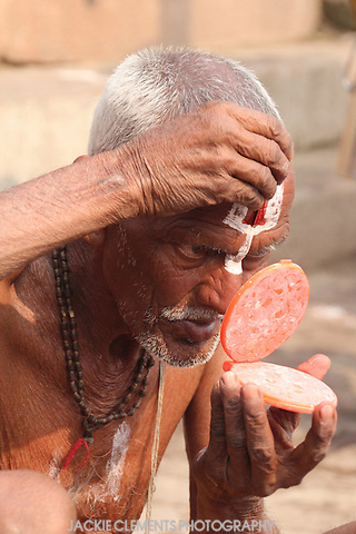 A devotee of the God Vishnu, identified by the tilak marking on his forehead,  reapplies after taking a bath in the holy waters of the Ganges.