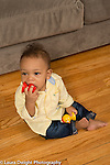 10 month old baby boy sitting full length looking to side as he holds and bites toy held to mouth