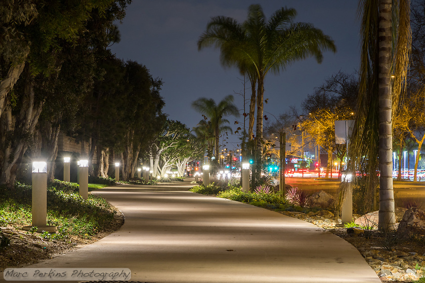 Lights line the pathway as we look north towards Merrimac Way along the Harbor Boulevard Cornerstone Bike Trail in Costa Mesa, California under a clear night sky.  The landscaping of the path, including a diversity of plants and rocks, can be seen.  The landscape architecture work on the project was done by David Volz Design.