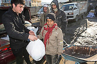 Activists from Afghan Action give out bags of childrens clothes to impoverished Afghan children. 2-1-13