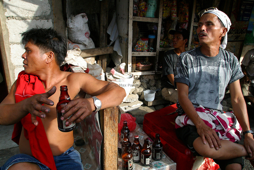 Men having beer at a store interrupted by a couple fighting. Baseco, Tondo, Manila. 13 January 2004