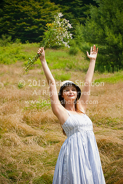Young woman standing in a field holding up a bouquet of wild flowers