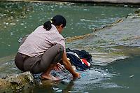 Woman washing clothes in the Yulong River, Yangshuo, Guangxi, China.