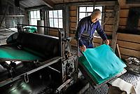Nederland Westzaan 2017.    De Schoolmeester te Westzaan is de laatste papiermolen ter wereld die op windkracht functioneert. De molen werd oorspronkelijk in 1692 gebouwd en is tegenwoordig nog dagelijks in gebruik. Er wordt op ambachtelijke wijze Zaansch Bord, een papiersoort, vervaardigd. De eigenaar is sinds 1976 de Vereniging De Zaansche Molen. De Papiermachine. Molenaar Arie Buttreman.  Foto mag niet voor reclame doeleinden worden gebruikt.   Foto Berlinda van Dam / Hollandse Hoogte