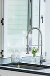 A modern faucet contrasts with the traditional white cabinetry and stone countertops.