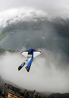 A jumper exits from the top of the mountain, into clouds. World BASE Race held in Innfjorden, Norway, where BASE jumpers in wingsuits compete in flying down the mountain. The winner is called the World's Fastest Flying Human Being..©Fredrik Naumann/Felix Features.