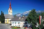 Austria, Tyrol, Igls near Innsbruck: parish church and tourist-office at village centre and Nordkette mountains