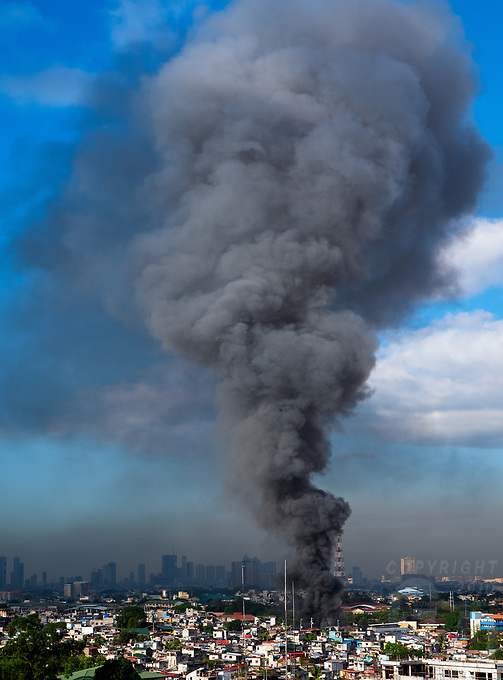 A very large fire and high plume of smoke over Manila, Philippines