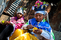 """Salvadoran boys, dressed as Moors and Christians, peel oranges during the Flower & Palm Festival in Panchimalco, El Salvador, 8 May 2011. On the first Sunday of May, the small town of Panchimalco, lying close to San Salvador, celebrates its two patron saints with a spectacular festivity, known as """"Fiesta de las Flores y Palmas"""". The origin of this event comes from pre-Columbian Maya culture and used to commemorate the start of the rainy season. Women strip the palm branches and skewer flower blooms on them to create large colorful decoration. In the afternoon procession, lead by a male dance group performing a religious dance-drama inspired by the Spanish Reconquest, large altars adorned with flowers are slowly carried by women, dressed in typical costumes, through the steep streets of the town."""
