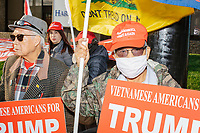 """A group stands on a street corner holding American flags, Back the Blue flags, and Trump campaign signs, including ones reading """"Vietnamese Americans for Trump 2020"""" before Eric Trump, son of US president Donald Trump, holds a Make America Great Again! campaign rally at the DoubleTree by Hilton Manchester Downtown in Manchester, New Hampshire, on Mon., Oct. 19, 2020."""
