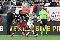 FOXBOROUGH, MA - JULY 25: Mathieu Choiniere #29 of CF Montreal dribbles as Christian Mafla #32 of New England Revolution pressures during a game between CF Montreal and New England Revolution at Gillette Stadium on July 25, 2021 in Foxborough, Massachusetts.
