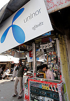 A small telecom vendor with large sign advertising for Uninor on a street in Mumbai. Telenor warned it could be forced to reconsider its presence in India if the New Delhi revises the terms of its spectrum licence amid a political scandal over regulation of the Indian telecoms industry.<br /> <br /> Unitech, since renamed Uninor, is one of five companies alleged to have benefited from irregularities that an official audit claimed had cost the Indian government $39bn in lost revenues from spectrum licences. <br />  <br /> <br /> Further reading : http://www.ft.com/cms/s/0/f391ebb0-33b4-11e0-b1ed-00144feabdc0.html#axzz1DWW1eUZh