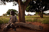 Opira Isaac (8), living with his grandmother, Achola Kelementina (age unknown). Isaac is HIV+ and lost his parents 5 years ago. His grandmother takes care of him and his 4 brothers and sisters. They live in Madi Opei, Uganda in a more secluded and less densely populated part of town. It is about a ten-minute walk from the health centre. ..When his father died of AIDS Isaac and his family were taken to his grandmother by his fathers family who did not want to take care of the children or the mother who was also suffering from AIDS. Kelementina took care of her daughter until she died. Then the family of her son-in-law came to pick up her body for the burial and left the children with her. Kelementina is living in her tukul with the 5 children and two of her older children. One of them is in his twenties and has polio so sits in a wheelchair. Unfortunately there are no tires on the chair anymore, so he cannot use it. He cannot do much during the day and drinks a lot. Kelementina says she cannot care for her household like she wants to because she is getting old and does not have much strength any more...When Isaac was about 3 or 4 years old he was sick all the time. He had Malaria, Diarrhea, fevers and rashes. He was brought to the HIV clinic and found out to be positive. Now that he is healthy again, he does not remember that he felt sick. His grandmother reminds him that he was never playing, always staying inside and very sad. She says it was very painful to see. Now that he is healthy, Kelementina hopes she will be alive for a very long time so that she can make sure he gets the care he needs and so she can look after him. If she would die now, she hopes her oldest grandson, who is in technical school, can find a job so he can look after Isaac. So far Isaac is the only one of the children who has been tested. Isaac goes to school and likes to draw and play football in the evening after he comes back from fetching water..