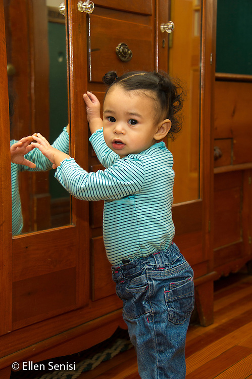 MR / Schenectady, NY. Portrait of toddler (1 year and 2 months old, African-American and Caucasian) in early walking stage standing and suporting herself on furniture. MR: Dal4. ID: AM-HD. © Ellen B. Senisi