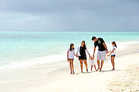 A family of five walking the sunny shore of Lanikai Beach, O'ahu.